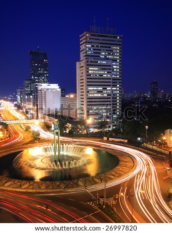 Night time view of traffic in the center of business district in Jakarta - stock photo