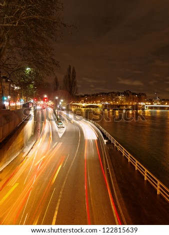 Night traffic along the Seine in Paris, capital of France, with car lights in motion blur.
