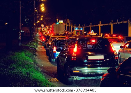 Night traffic jam on a city street: the slow movement of cars with red stop signals. - stock photo