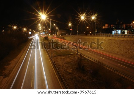 Night traffic light trails created by red rear and white headlights of vehicles moving on two-way motorway - long exposure