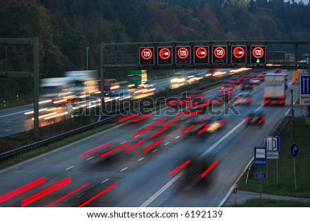night traffic on autobahn with speed limit sign, motion blur - stock photo