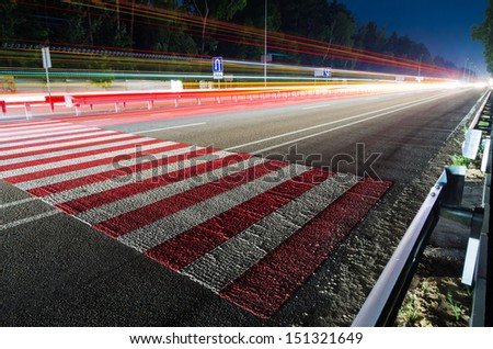 Night traffic with pedestrian crossing and tracers from cars - stock photo