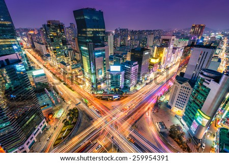 Night traffic zips through an intersection in the Gangnam district of Seoul, South Korea. - stock photo