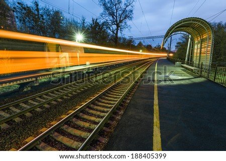 Night train in motion blur showing light trails at the station - stock photo
