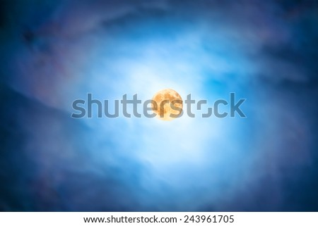 Night view at the full moon through moving blue clouds. Abstract scene - stock photo