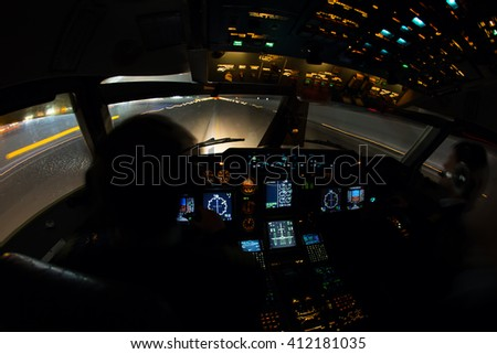 Night view from the airplane cockpit. The aircraft is moves for take off from the airport runway. - stock photo