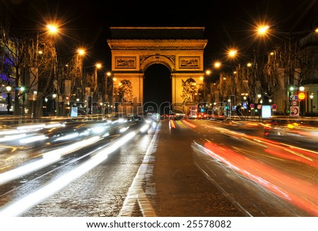 Night view looking up the Champs-Elysees at the Arc de Triomphe in Paris, France.