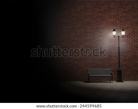 Night view of a brick wall, vintage street light and bench - stock photo
