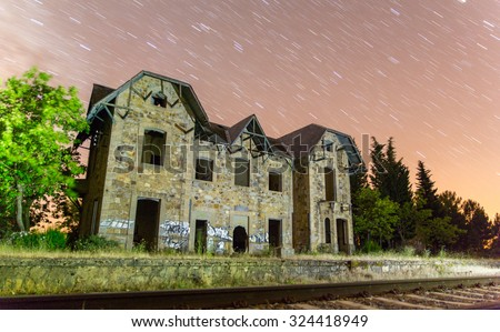 Night view of abandoned train station with star trails - stock photo