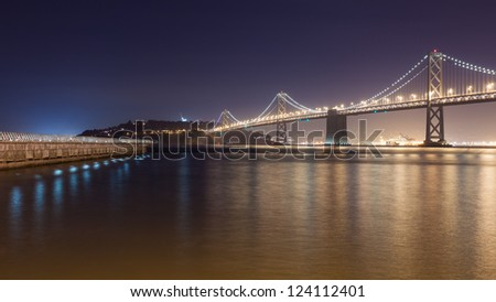 Night view of Bay Bridge and a pier in San Francisco. - stock photo