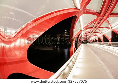 Night view of Calgary's Peace Bridge. The bridge features a red and white helix design. Opened in March 2012, it connects the extensive Bow River Pathway on the north and south sides of the Bow River. - stock photo