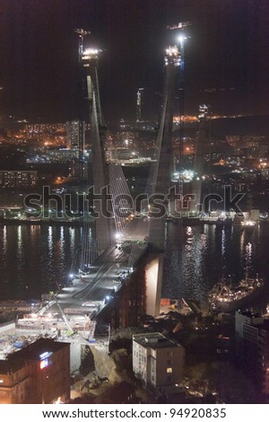 night view of construction of big guyed bridge in the Russian Vladivostok over the Golden Horn bay - stock photo