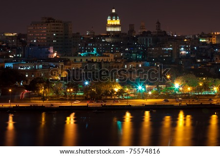 Night view of Havana including the Capitol, other famous buildings and the bay with reflection on the water - stock photo