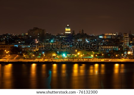 Night view of Havana with reflections on the bay and the illuminated dome of the Capitol in the background - stock photo