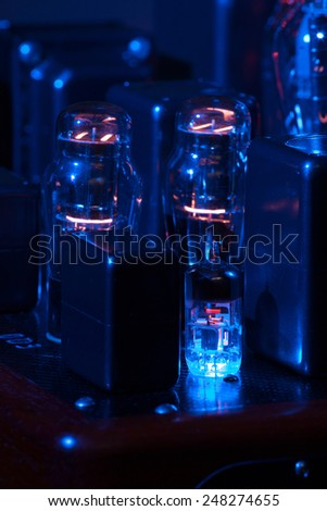 Night view of hi fi amplifier with electronic vacuum tubes with incandescent filament. Grazing blue light - stock photo
