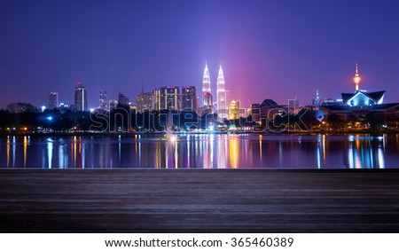 Night view of Kuala Lumpur city with stunning reflection in water and wooden board - stock photo