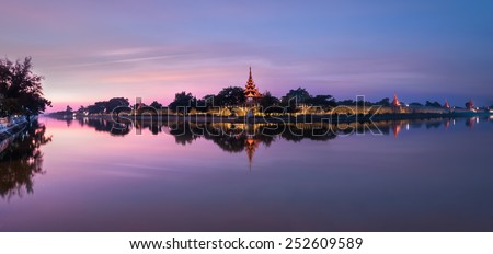 Night view of Mandalay cityscape with famous Fort or Royal Palace. Myanmar (Burma) travel landscapes and destinations. Three images panorama - stock photo