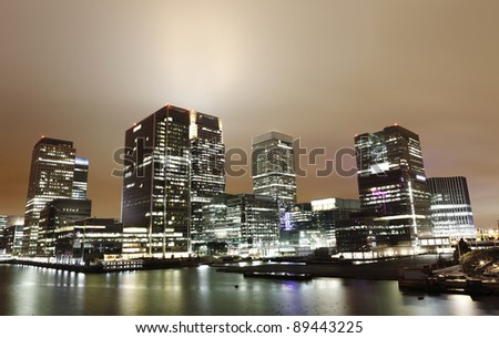 Night view of modern skyscrapers  lighting up a misty sky in Canary Wharf, London's major financial district at the London Docklands at Isle of Dogs. - stock photo