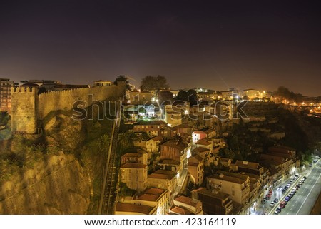 Night view of Porto funicular railway, house roofs with illumination