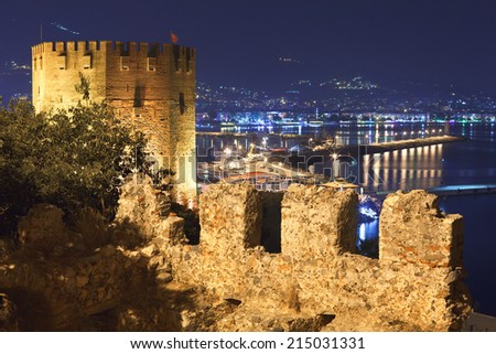 Night view of Red Tower (Kizil Kule) and ancient stone wall of Alanya Castle, Turkey - stock photo