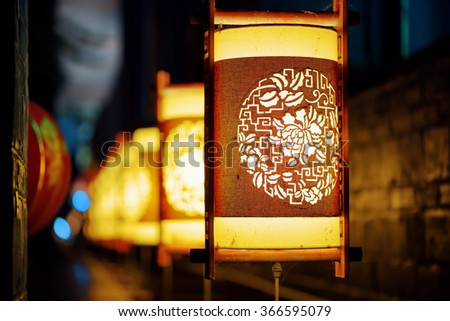 Night view of row of traditional Chinese street lanterns in the Old Town of Lijiang, Yunnan province, China. Lijiang is a popular tourist attraction of Asia. Focus on the first lantern. - stock photo