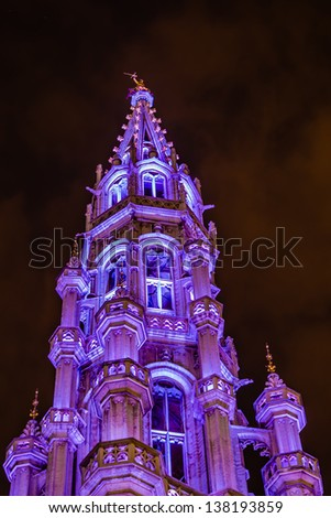 Night view of the ancient Town Hall illuminated in purple, in Grand Place, Brussels, Belgium. - stock photo