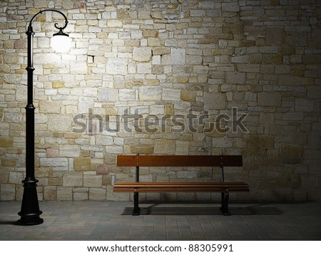 Night view of the illuminated brick wall with old fashioned street light and bench - stock photo