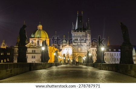 night view of the illuminated charles bridge in prague with church of saint francis of assisi and church of the holy saviour