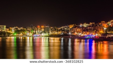 night view of the illuminated old town of bulgarian city sozopol which is dominated by reconstructed ancient wall dividing city from the black sea.
