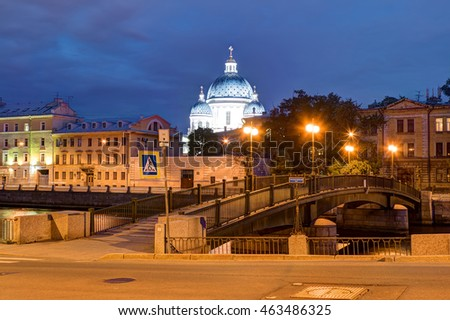Night view of the Krasnoarmeysky Bridge and the dome of the Trinity Cathedral behind buildings on the embankment of Fontanka River, St. Petersburg, Russia