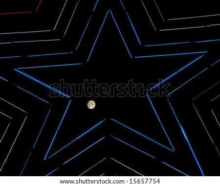 Night view of the moon transiting through the Mill Mountain Star in Roanoke, Virginia. - stock photo
