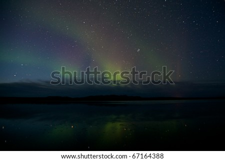Night view of the northern lights over a lake in Alaska. - stock photo
