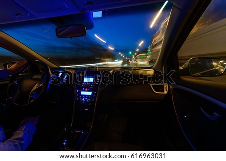 Night view of the road from inside the car. A natural light street and other cars are blurred. The hands of an elderly man