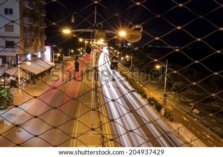 Night view of the seaside pedestrian bridge connecting the beach to GSO Sports park in Limassol,Cyprus.A view of the cable that lovers hang padlocks,the traffic on the street and the mediterranean sea - stock photo
