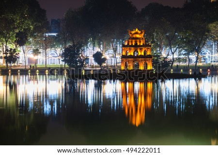 Night view of the Turtle Tower or Tortoise Tower reflection in Hoan Kiem Lake (Lake of the Returned Sword) at historic centre of Hanoi, Vietnam. The tower is located on an island in the middle of Lake