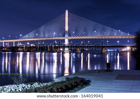 Night view of the Veterans' Glass City Skyway bridge in Toledo Ohio.  The bridges center pylon is lit up with LED lighting and the stainless steel cables are lit with floodlights. - stock photo