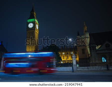 Night view on London landmarks Big Ben Clock and motion blur of double decker red bus - stock photo