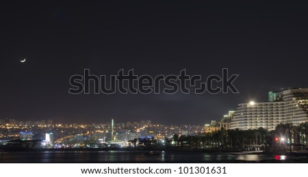 Night view on resort hotels of the northern beach of Eilat - famous Israeli city with hotels and marine beaches packed with thousands of tourists from around the world - stock photo