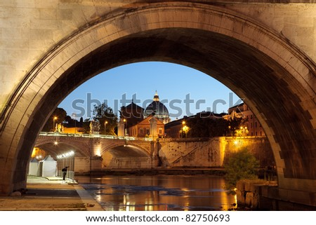 Night view on Saint peter cathedral of the Vatican, Rome, Italy, seen from under a bridge over the tiber river - stock photo