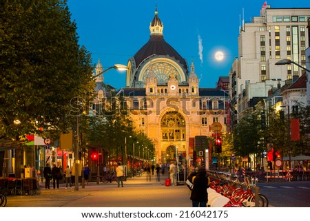 Night view on the street leading to the exterior of Antwerp central railway station at dusk, with deep blue sky and a bright shining moon, and people having a drink at the  terraces along the alley - stock photo