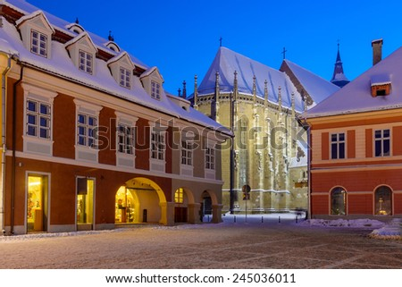 Night view over Brasov's most important landmark, the Black Church, the largest Gothic church between Vienna and Istanbul, towers over Piata Sfatului and the old town. Winter time with snow - stock photo