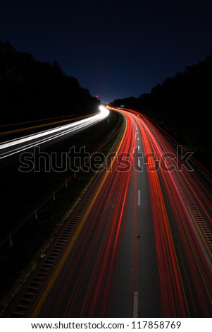 Night white headlights and red tail lights disappearing over the horizon - stock photo
