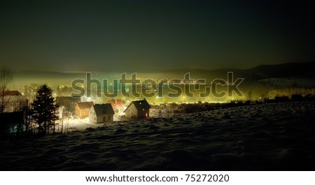 Night winter view on the small town with mist - stock photo