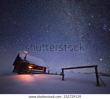 Night with stars. Christmas landscape. Wooden house in the mountain village - stock photo