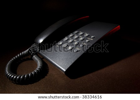 Night work - corded phone on brown table background lighted with red