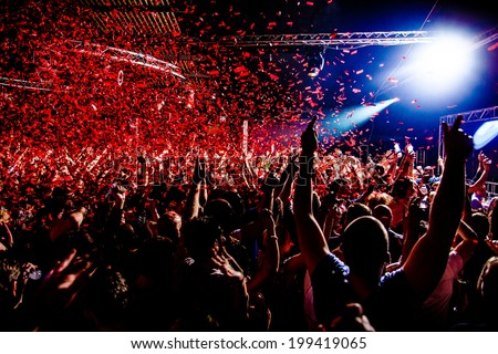 Nightclub party clubbers with hands in air and red confetti - stock photo