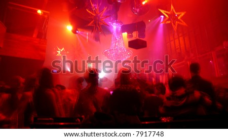 Nightclub scene with christmas decor and dance floor crowd in motion - stock photo