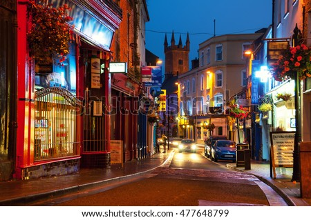 Nightlife at the medieval old part of the popular touristic city Ennis, Ireland. It hosts many restaurants and bars, blurry people at the street