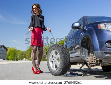 Nightlife dressed woman repairs car. Leggy lady dressed in red miniskirt pantyhose high heels shoes stays next to broken car and keeping spare tire and tools - stock photo