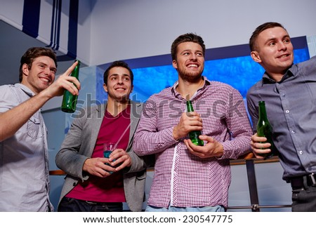 nightlife, party, friendship, leisure and people concept - group of smiling male friends with beer bottles drinking in nightclub - stock photo